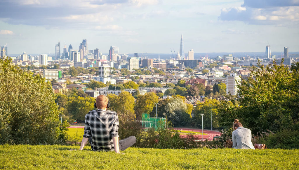 People sitting in a green space overlooking the city of London