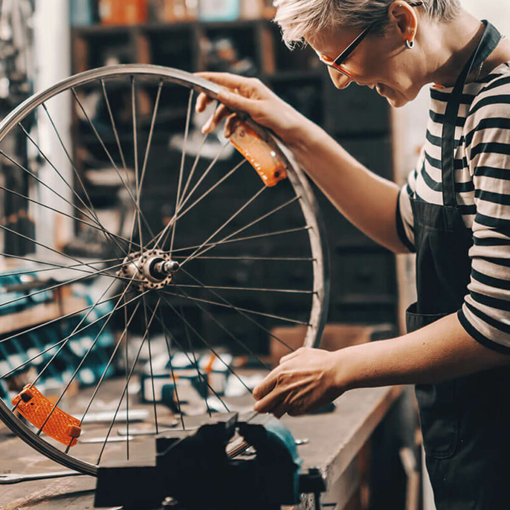 a woman repairing a bicycle wheel