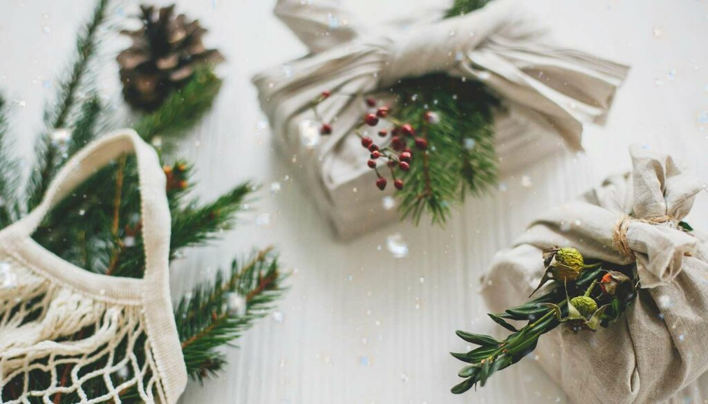 gifts wrapped in sustainable reusable cloth with pine cones and fir