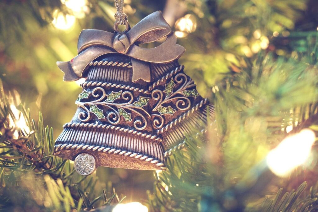 metal baubles in shape of bell with ribbon hanging with a christmas tree background
