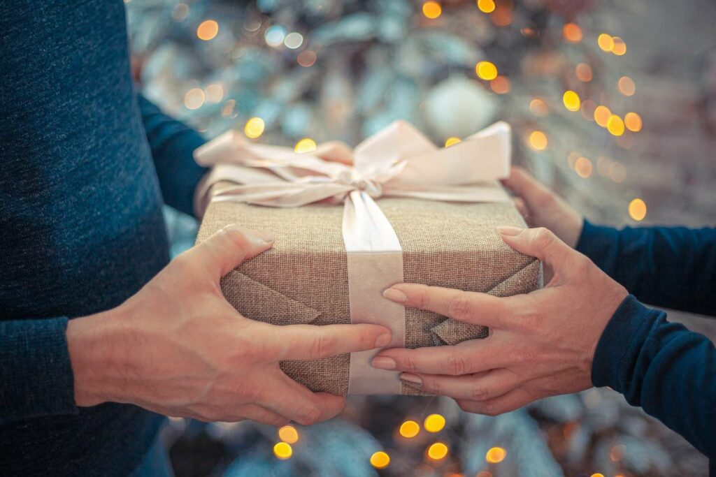 two hands holding a gift wrapped in brown hessian with twinly lights in the background