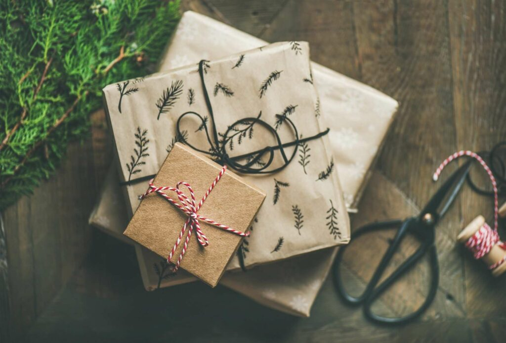 presents underneath a christmas tree wrapped in brown paper and tied with string